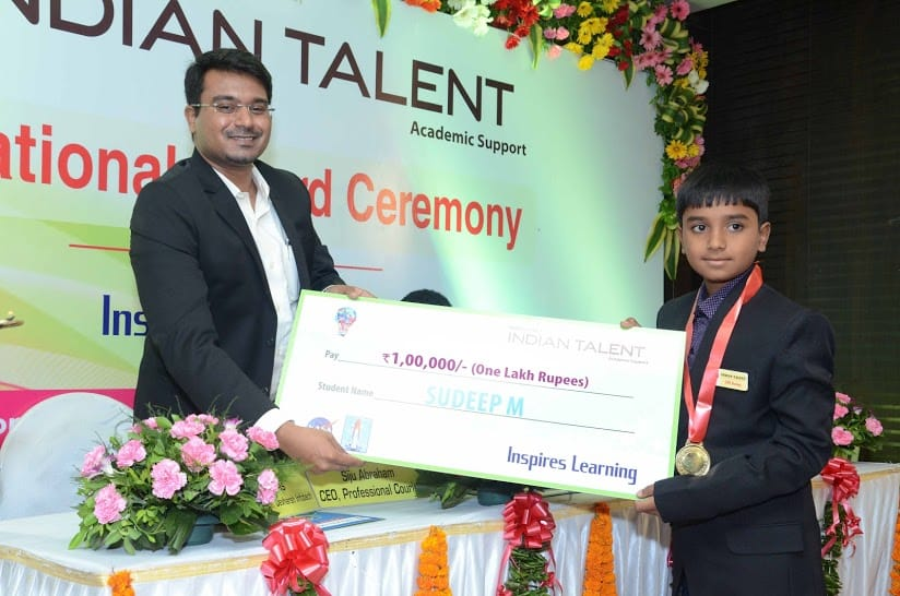 uploads/Olympiad-functions-and-Organization/Teacher Holding Cheque.jpg